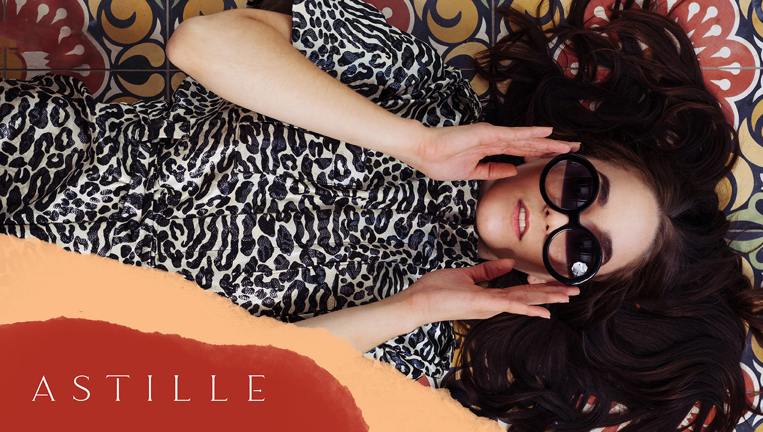 Astille model in animal print boiler suite with supporting graphics and brand logo