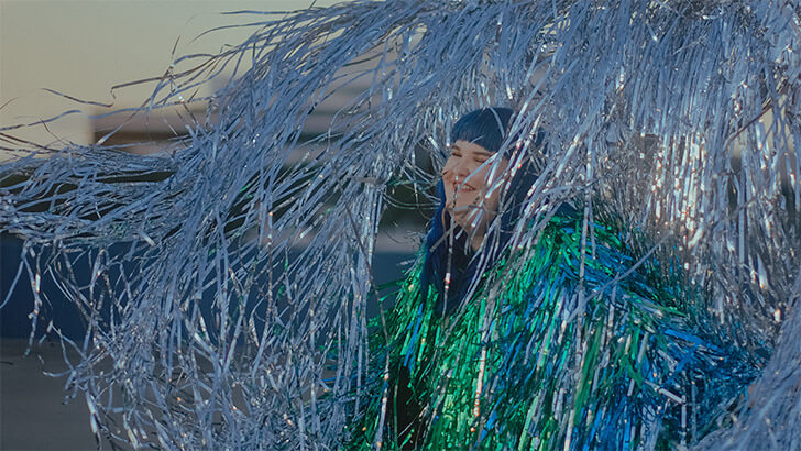 A blue haired woman in a green tinsel jacket laughs amidst a silver tinsel wall on a roof top as the sun sets in the background.